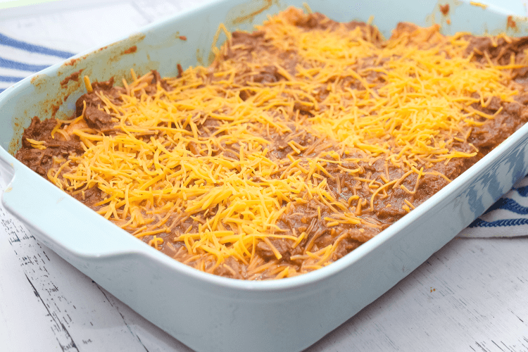 A pan of Tex Mex cheese enchiladas with enchilada chili gravy ready to go in the oven