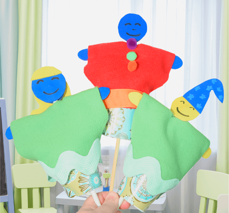 Three paper cup puppets held in one hand in front of a window.