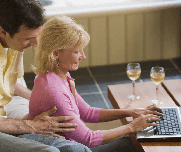 A man and woman sitting at the coffee table with a laptop and two glasses of white wine.