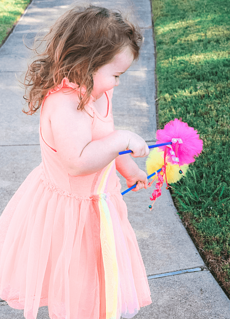 A side view of a little girl laughing, wearing a fairy dress, and holding two fairy wands.