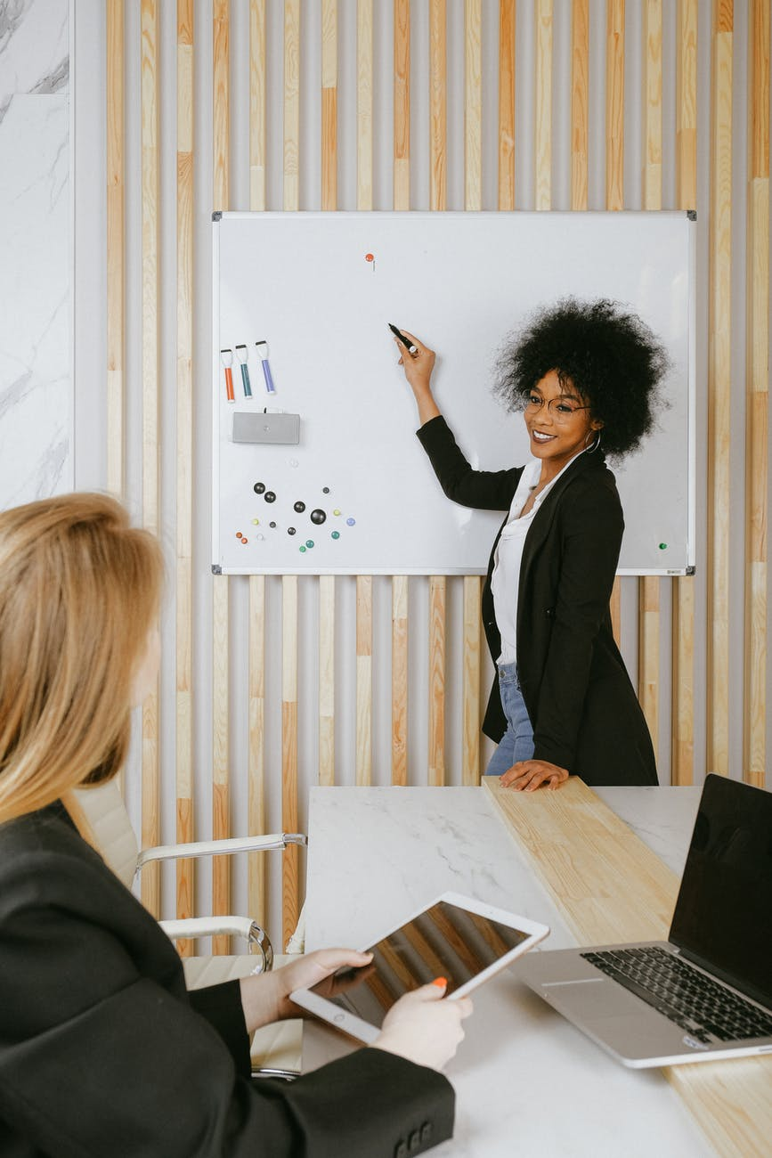 woman pointing at whiteboard