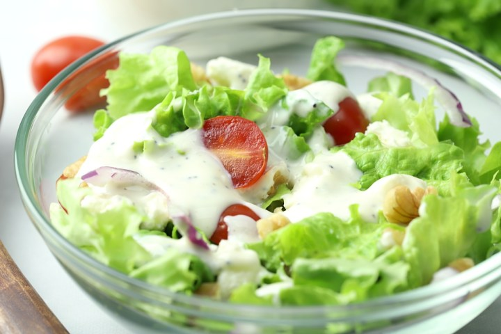 A salad coated in a creamy dressing.