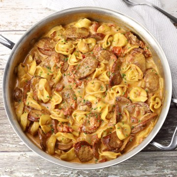 Saute pan filled with tortellini and sausage.