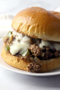 Close up of ground beef, onions, and bell pepper in a sloppy joe sandwich.
