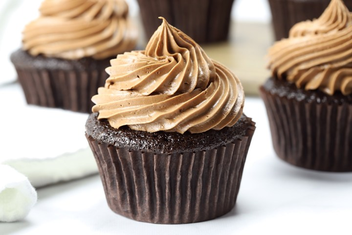 Chocolate cupcakes sitting on a white counter top.