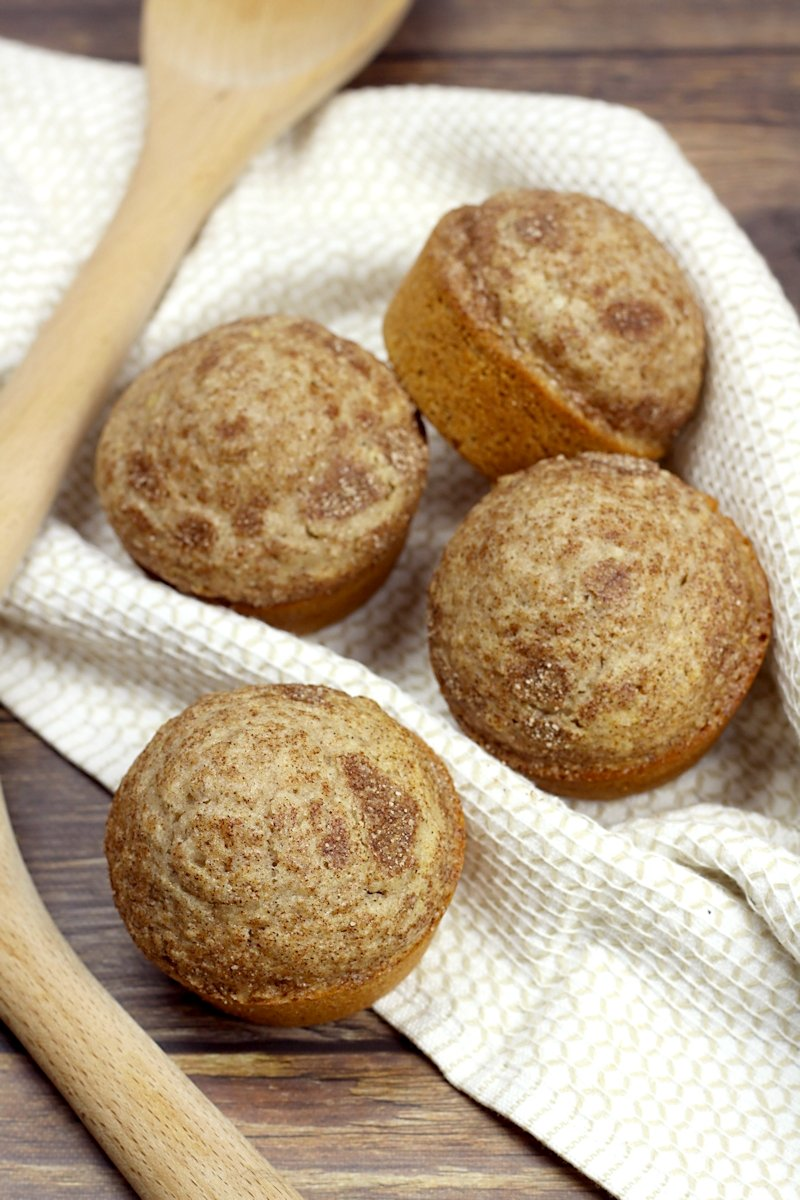 Cinnamon muffins with a tea towel on a counter top.
