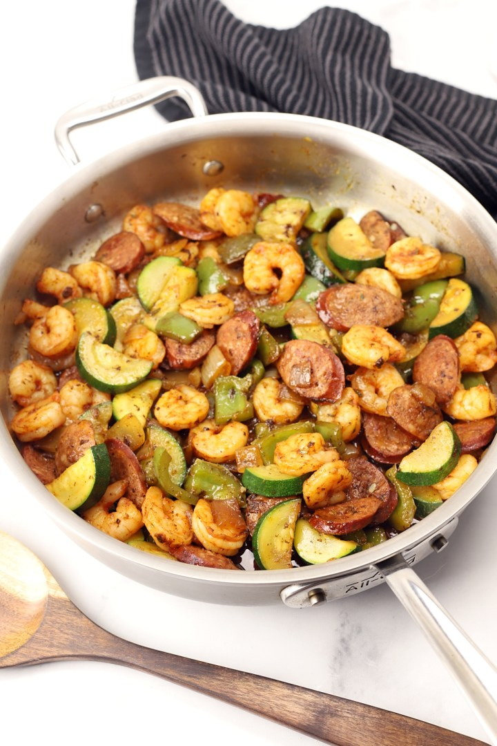 A saute pan filled with shrimp, sausage, and veggies.