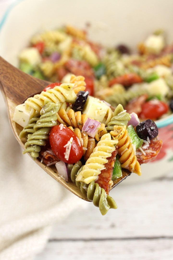 A spoonful of classic pasta salad with rotini, cherry tomatoes, olives, pepperoni, and mozzarella cheese.