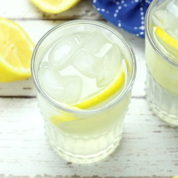 Glss of lemonade on a white wood countertop, with lemon wedges and a blue kitchen towel