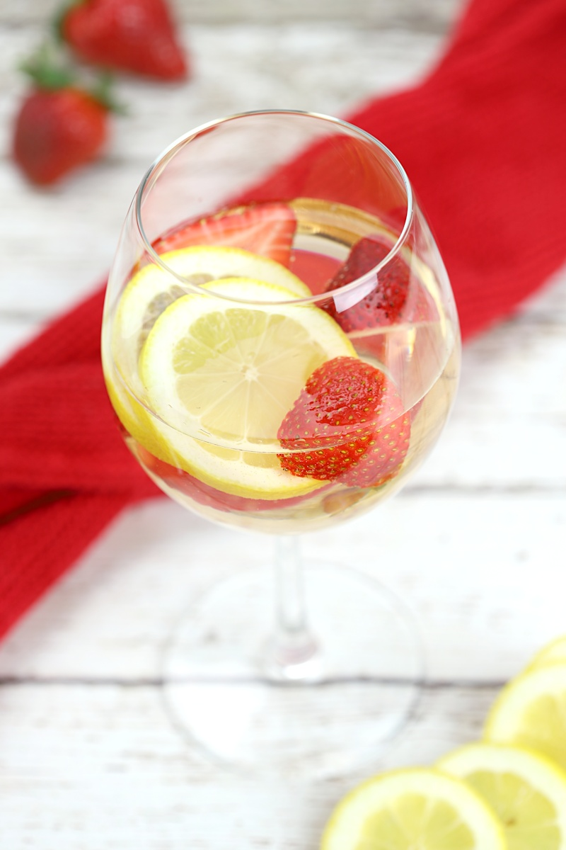 A glass of sangria, with a red kitchen towel, lemon slices, and strawberries on a white wood countertop.