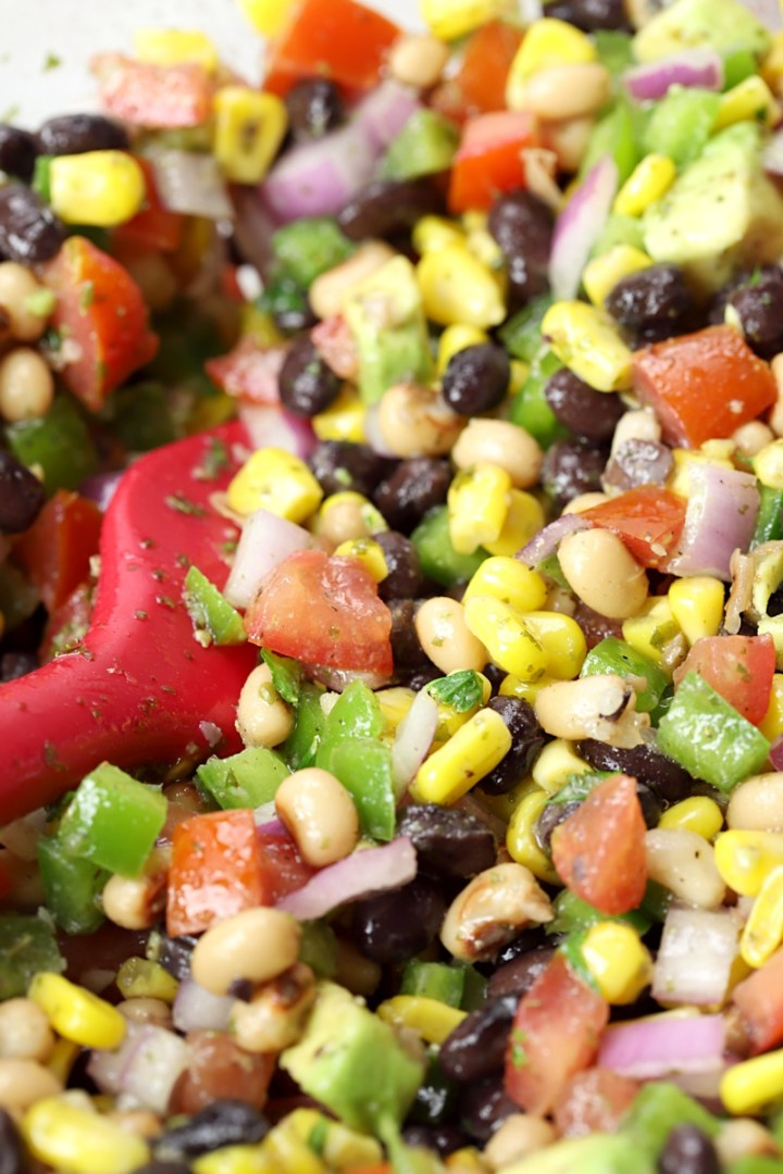 Close up of black beans, black eyed peas, corn, and peppers.