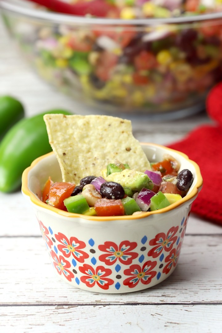 A single serving dish of cowboy caviar with a tortilla chip.