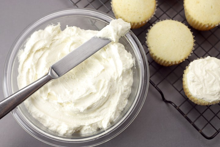 Knife and bowl of buttercream frosting, with unfrosted cupcakes.