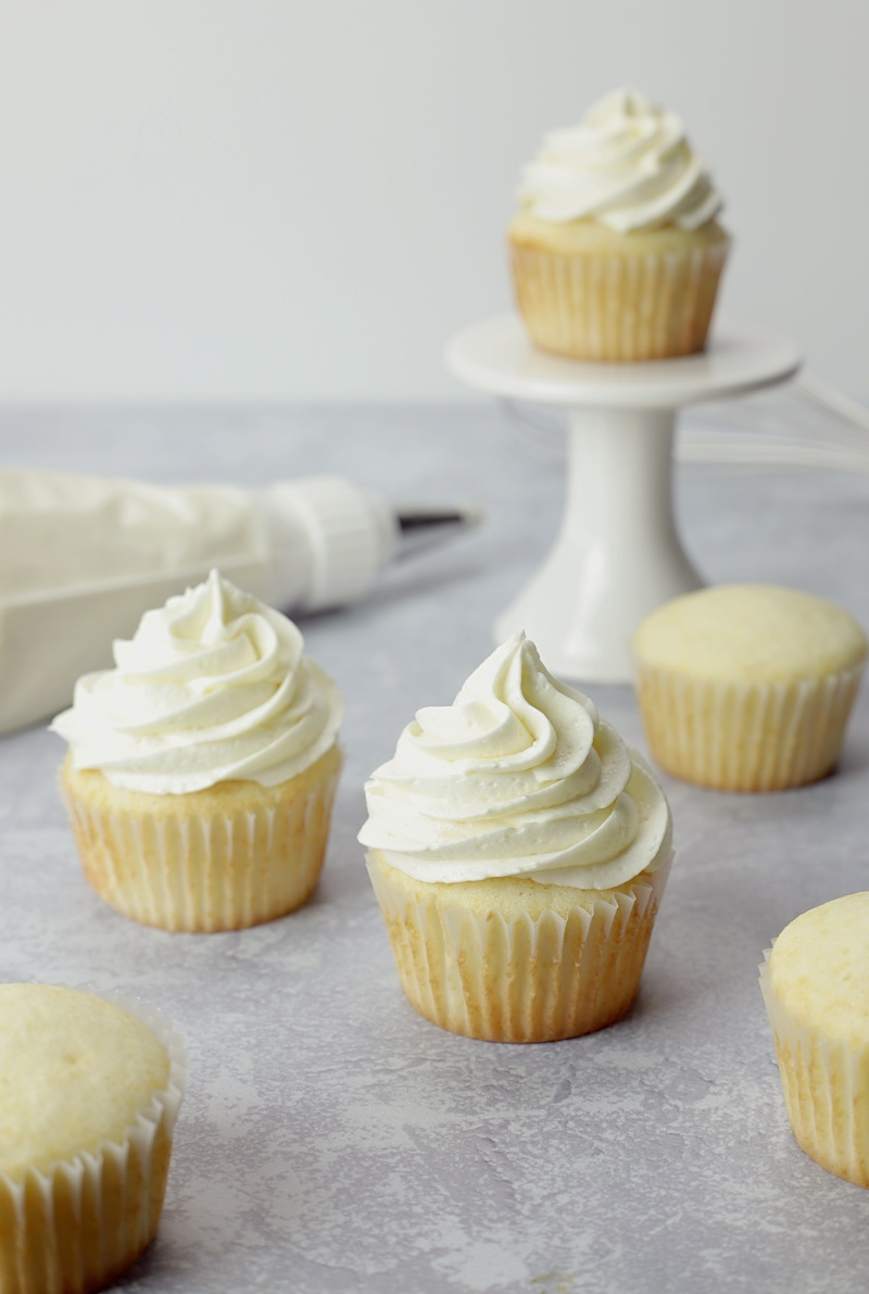 Cupcakes on a grey counter top with a frosting piping bag.
