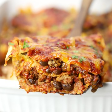 Serving of beef enchilada casserole on a wooden serving spatula.