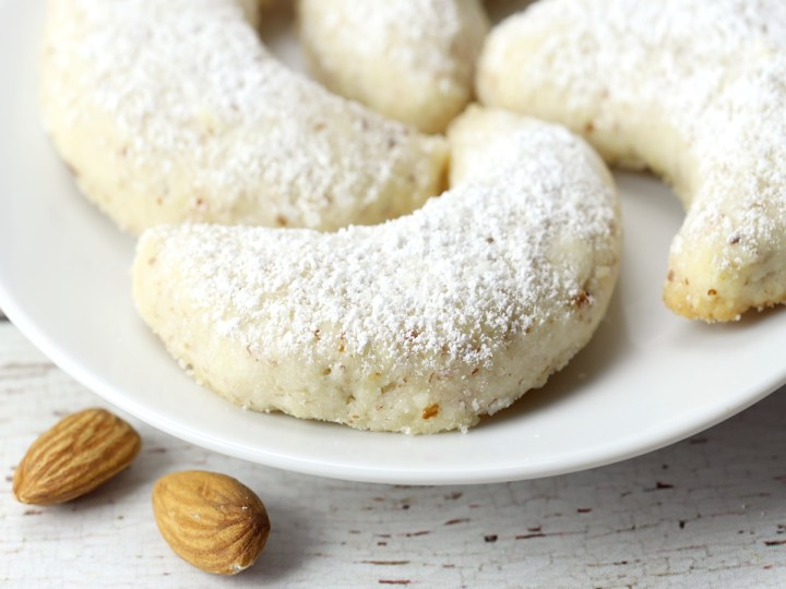 Powdered sugar dusted on top of a vanilla crescent cookie.