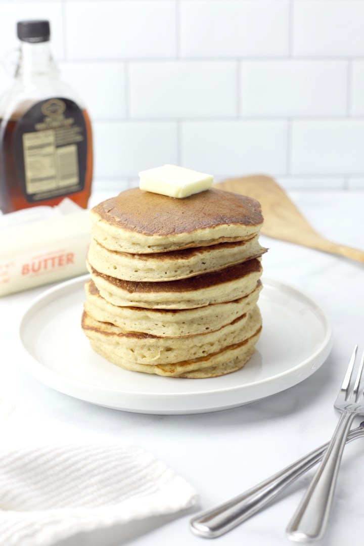 A stack of applesauce pancakes with a pat of butter on top.