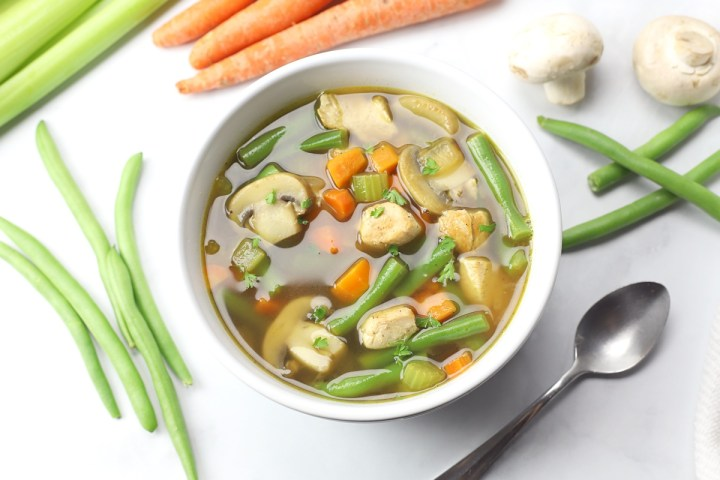 Mushrooms, green beans, chicken, carrots, floating in chicken broth.
