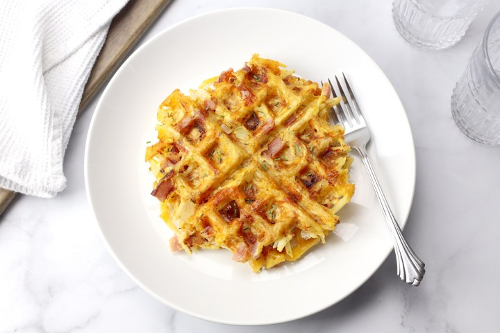 Hash brown waffles on a white plate with a fork.