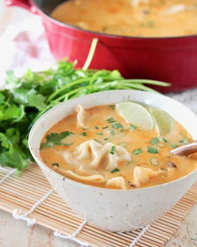 Soup with chicken potstickers and a lime wedge.
