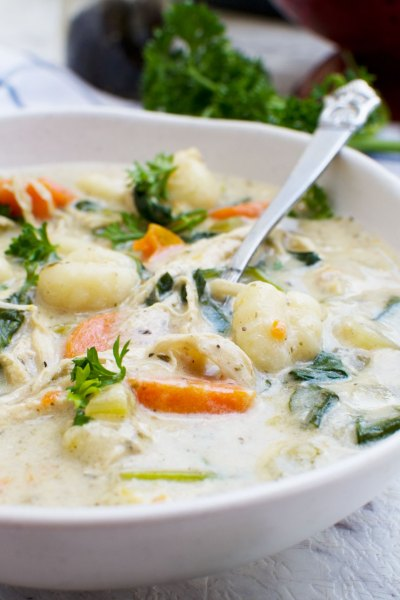 Soup with chicken, vegetabls, and gnocchi in a white bowl with a spoon.