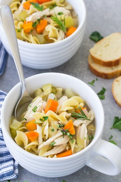 Chicken noodle soup in white soup bowls.