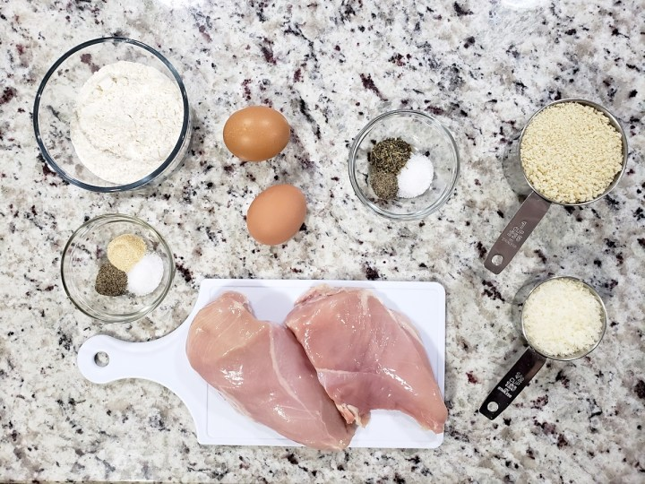 Chicken breasts and other ingredients on a counter top.