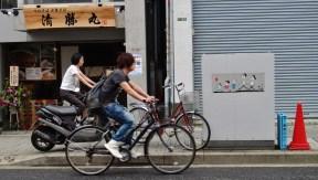 A pair of people on bikes in Sakurashinmachi, Tokyo, near a graphic of the Sazae-san family.