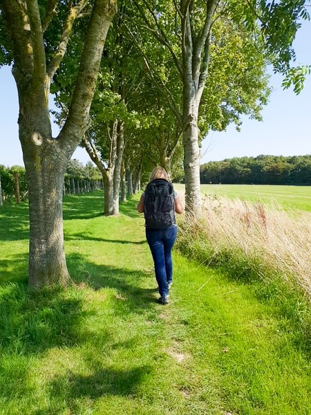 woman with backpack walking through trees