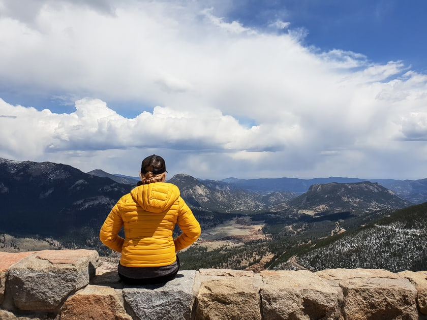 woman in yellow jacket looking at rocky mountain national park