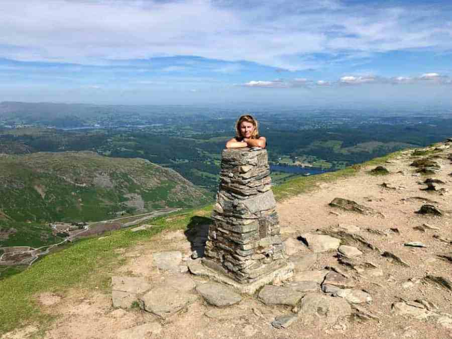 woman looking over Coniston Old Man Trig point