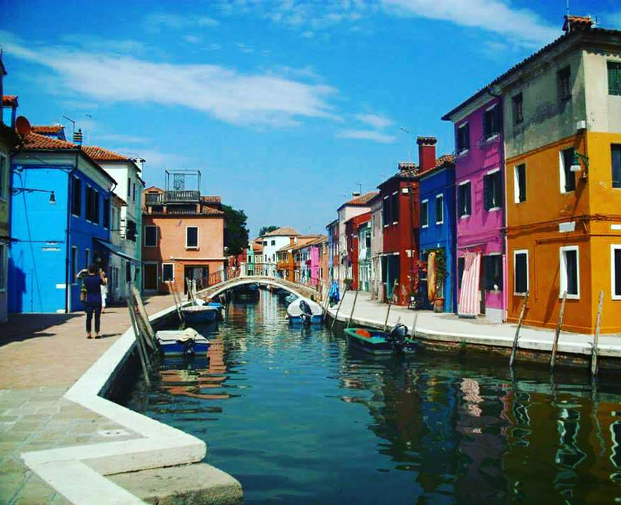 A canal with a bridge in the distance on the Venetian Island of Murano. Either side of the canal are multi-coloured brightly painted fisherman's houses