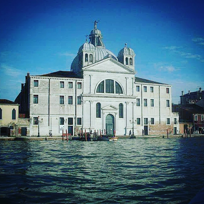 Le Zitelle Church in Venice. A large white building with large glass windows, blue door and grey domed roof. The church is situated on the edge of water