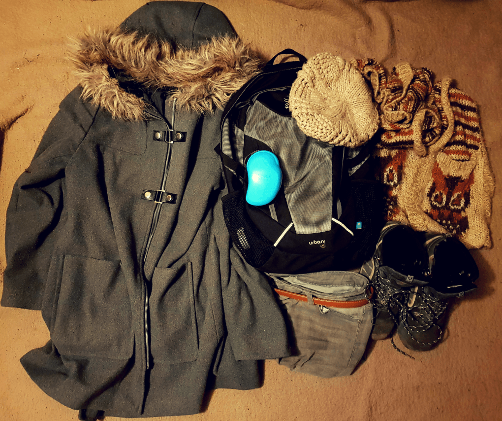 A black and grey back used for carry on luggage for 3 days in Brussels. A grey winter coat with brown fur around hood, brown wool hat and scarf, brown and grey hiking boots, grey jeans and a tangle teaser hair brush.