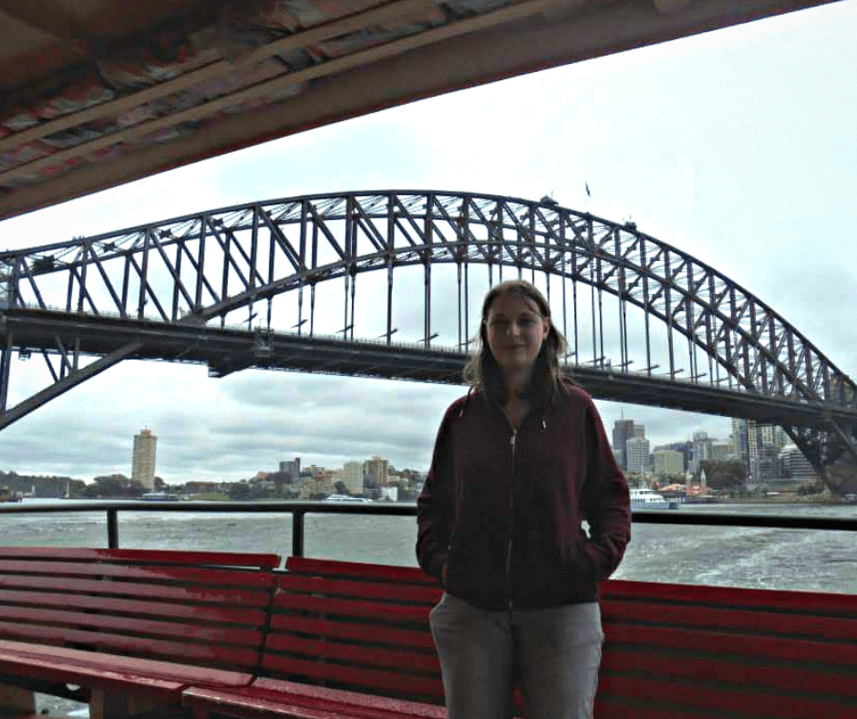 A woman (me) wearing red hoodie and grey jeans stood up on a ferry with red chairs and a balcony behind. Over the balcony the Sydney harbour can be seen including the harbour bridge