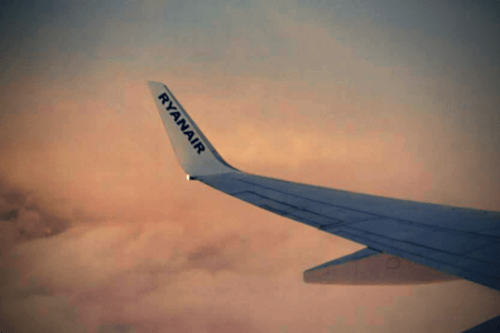Ryanair hand luggage policy changes. A Ryainair plane wing above the clouds at sunset taken through the airplane window.
