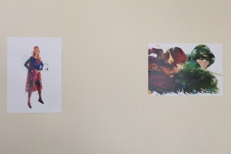 A painting of Supergirl in the classic red and blue costume next to a painting of the Flash in red fighting Green Arrow