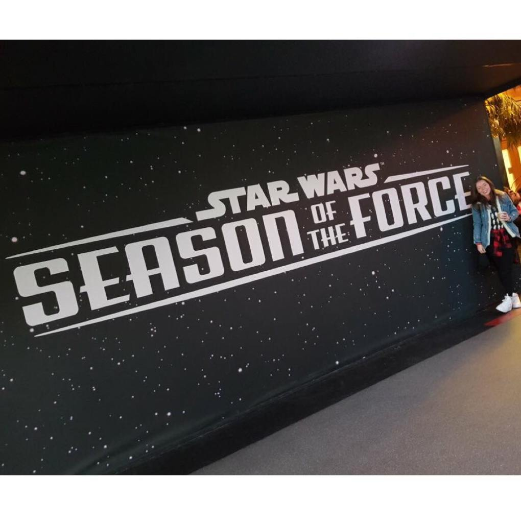 A black wall with white stars on it with Star Wars, Season of the Force written on it with a girl standing in front