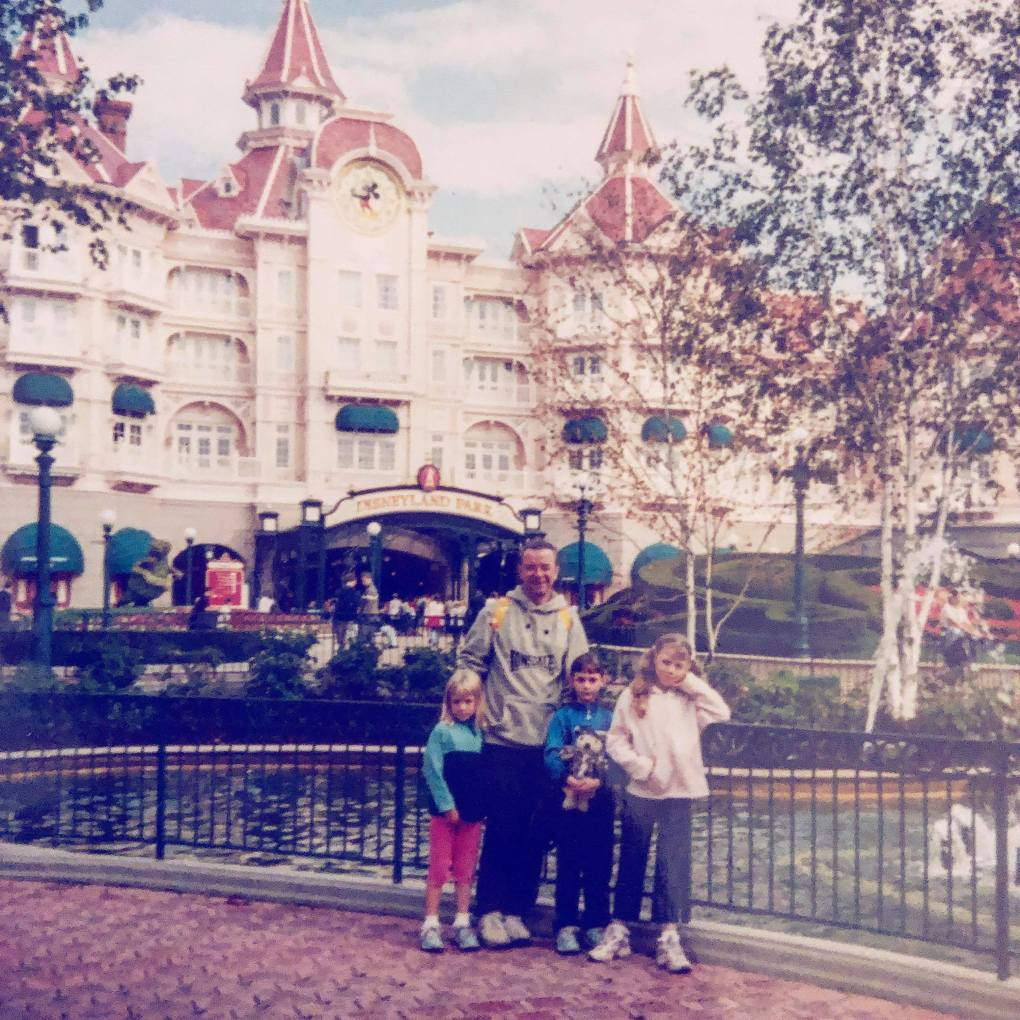Old family photo of 3 young girls and their dad at Disneyland Paris in front of the Disneyland Hotel