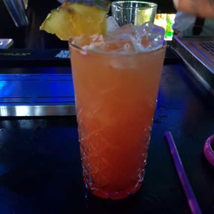 Orange and Red drink in a tall glass with ice and a pineapple slice served in the bar at Andwhynot Mansfield
