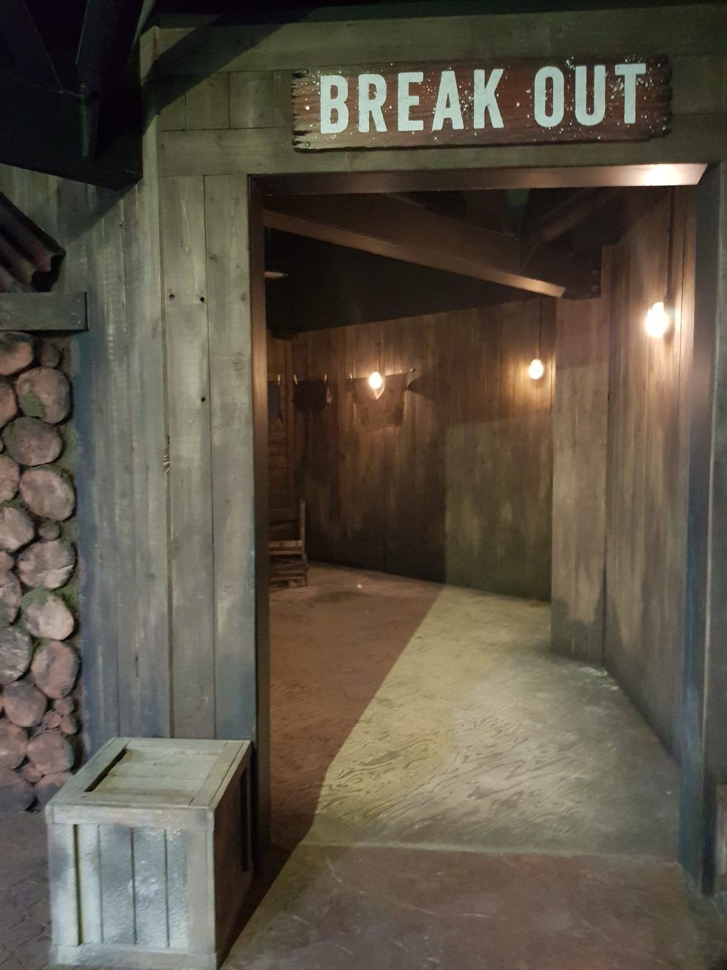 Entrance to the Break out escape room at the Bear Grylls Adventure. A Wooden door frame with BREAK OUT written above leading into a wooden corridor with a small wooden box outside