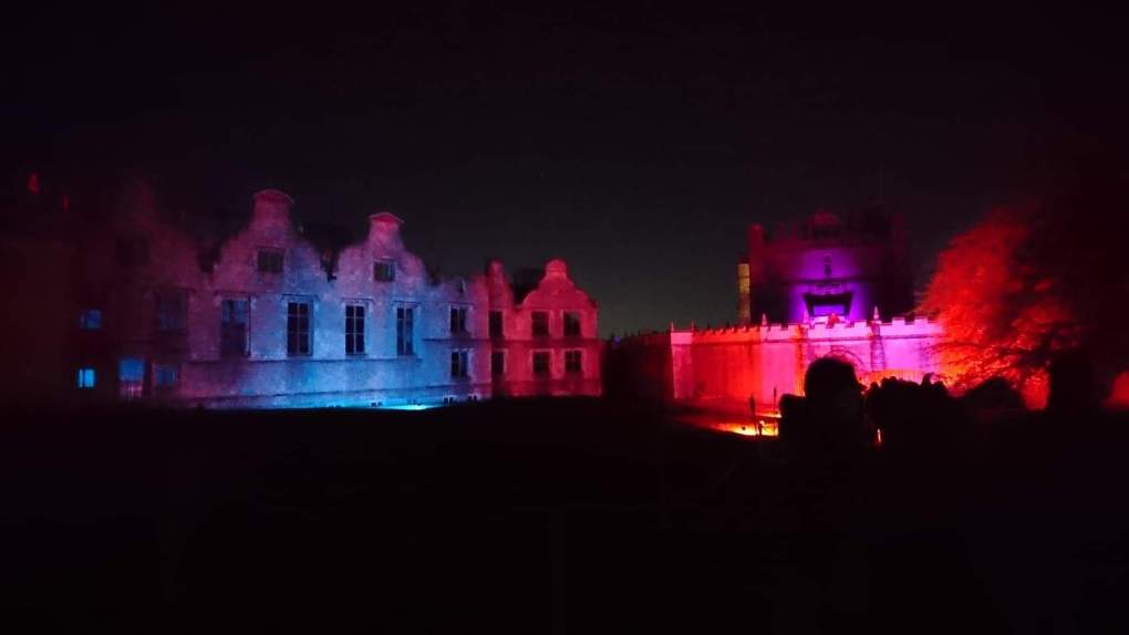 A night time shot of the ruins of Bolsover Castle and the little castle lit up with eerie purple lighting on Halloween Night