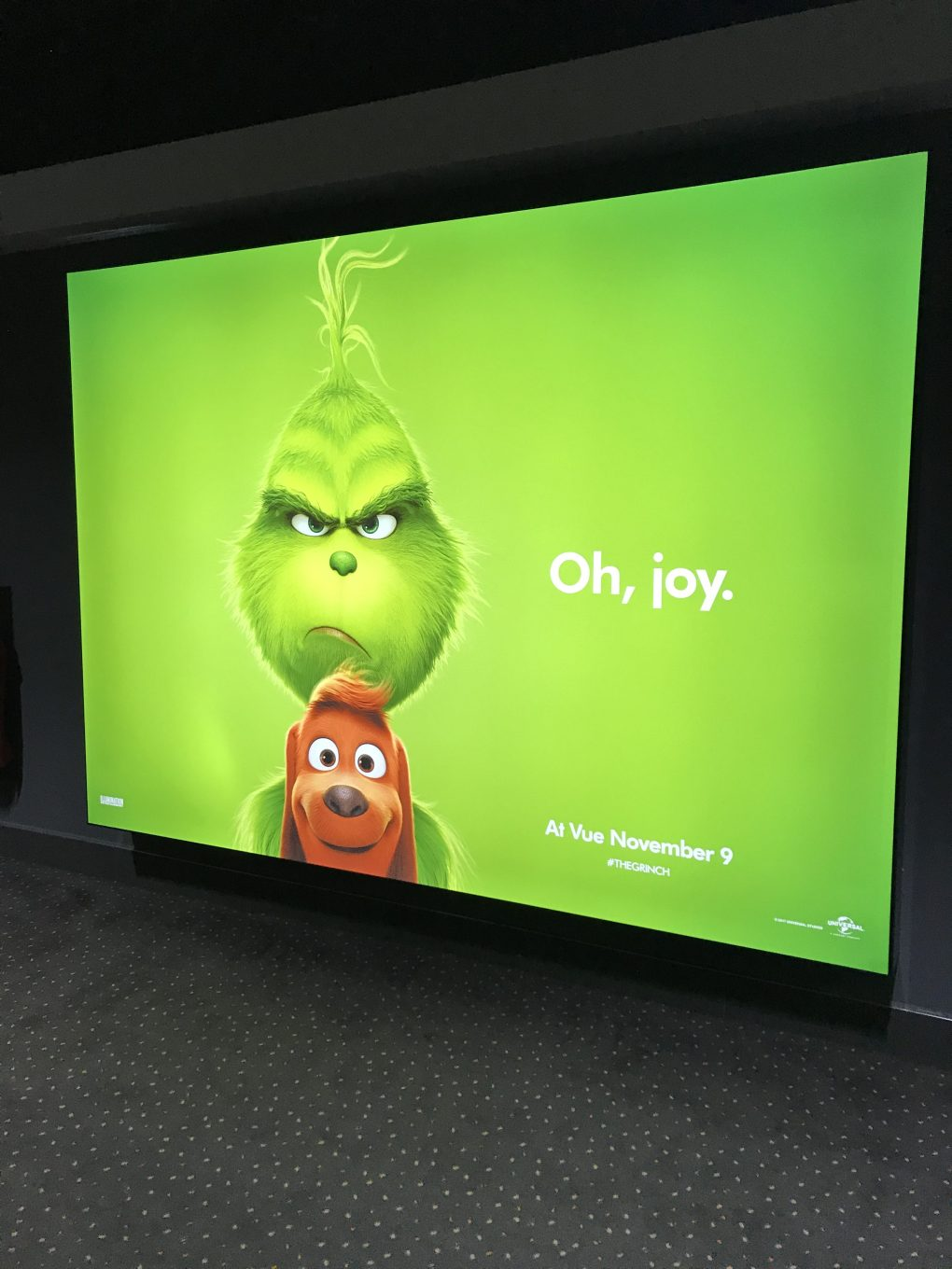 A poster for the Grinch Christmas film. The background is green with a cartoon version of the Grinch, (a green furry creature with an angry expression) holding a brown dog. Next to the Grinch it says 'Oh Joy.'