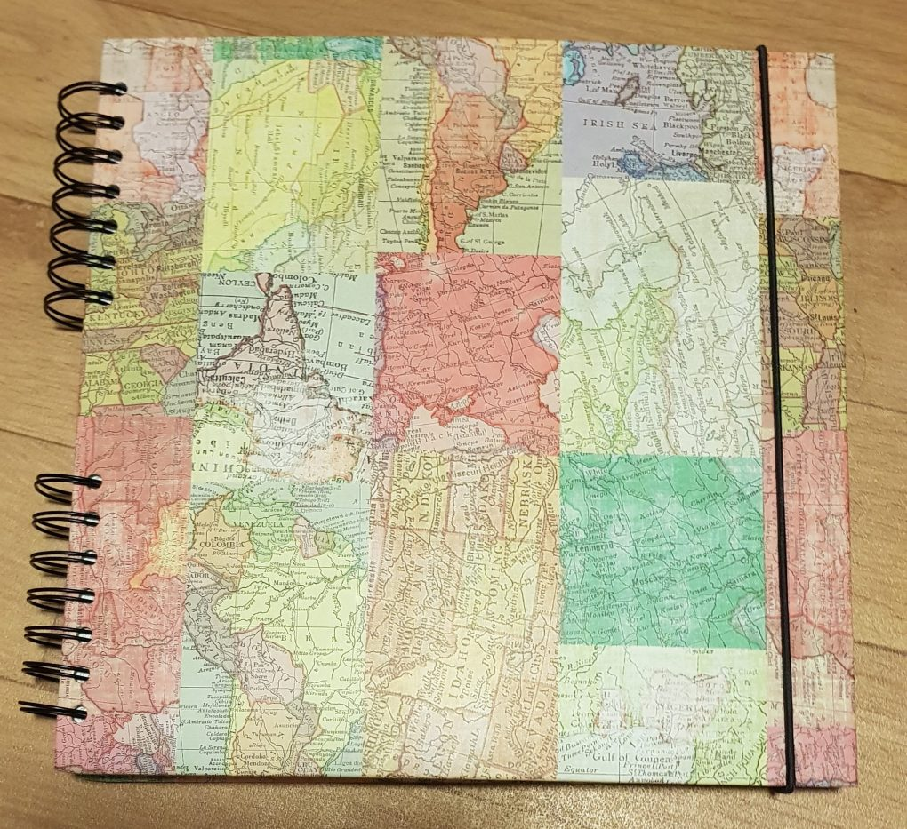 A scrapbook with multicoloured sections of different maps in a patchwork pattern on the cover and a black elastic string holding it shut.