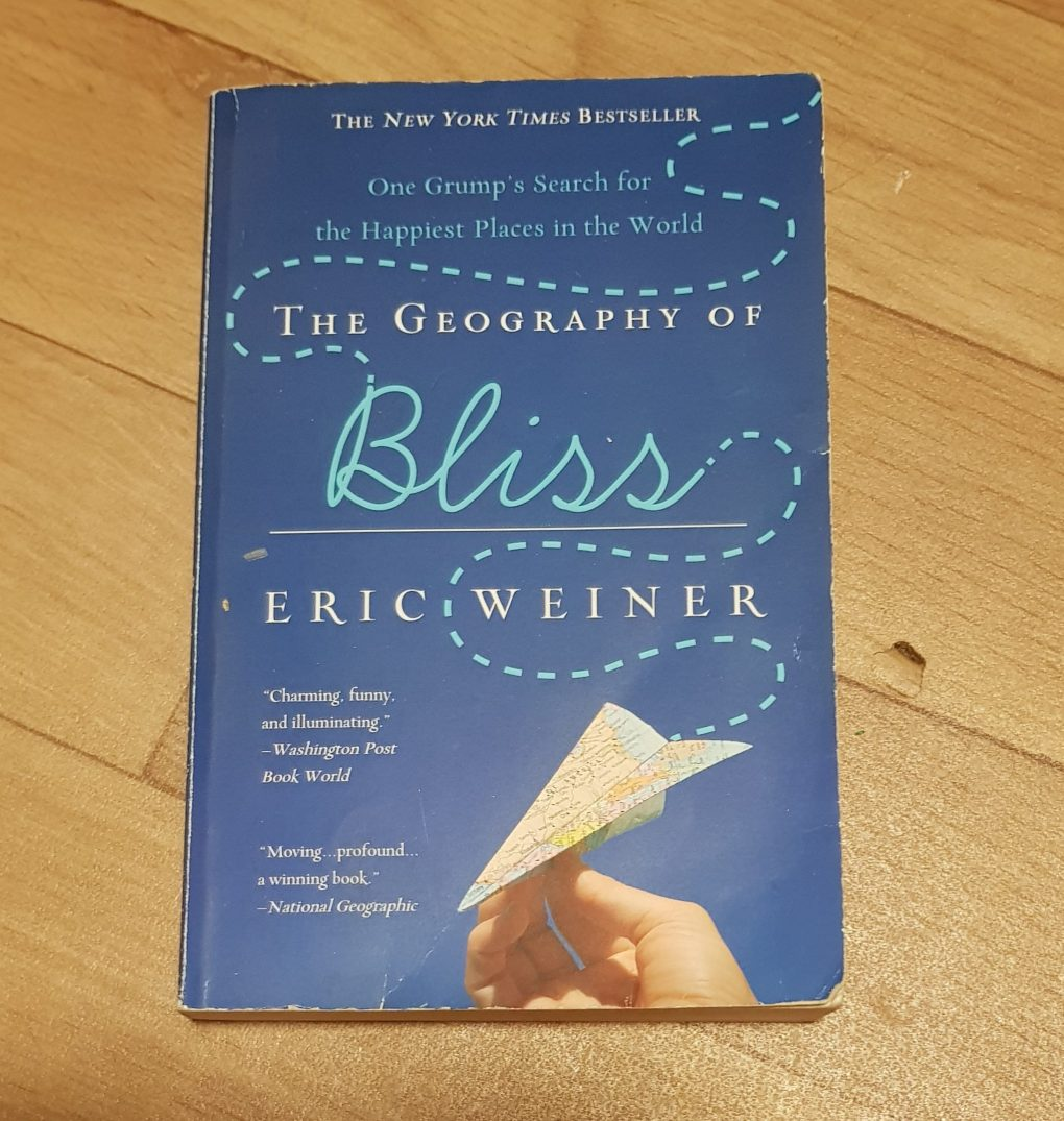A blue book with a hand holding a paper aeroplane. The writing says The Geography of Bliss, one Grump's search for the happiest places in the World