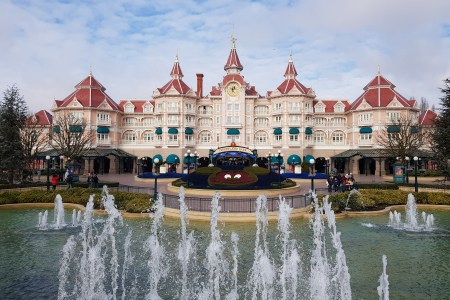 The Disneyland Hotel at Disneyland Paris. A pale pink castle shaped building with dark pink roof. A red mickey mouse head is made out of flowers in a circular flower bed and a small lake with fountains shooting water upwards was in front of the building