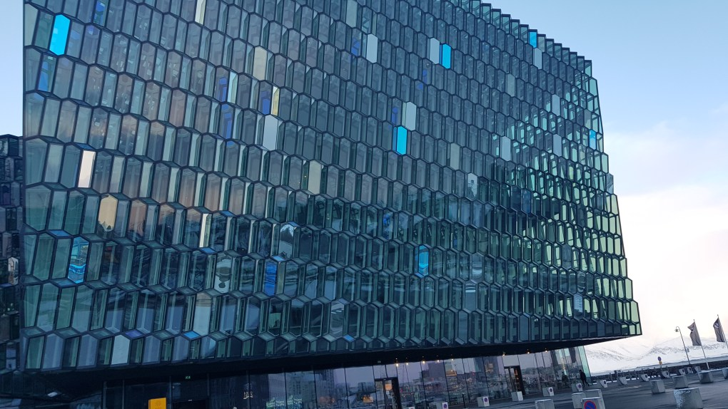 A large glass building with a honeycomb effect of windows across the entire building