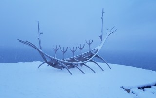 The Sun Voyager statue in Reykjavik, Iceland. A statue made of metal to look like a viking ship with snow all around