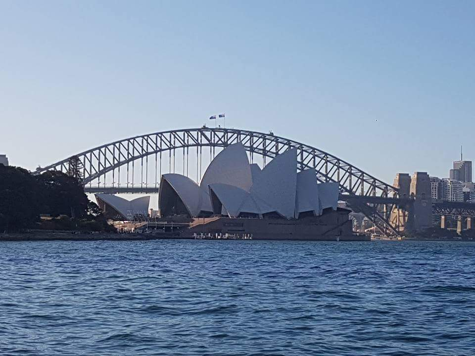 A view of the Sydney Harbour with the Sydney opera house in front of the harbour bridge