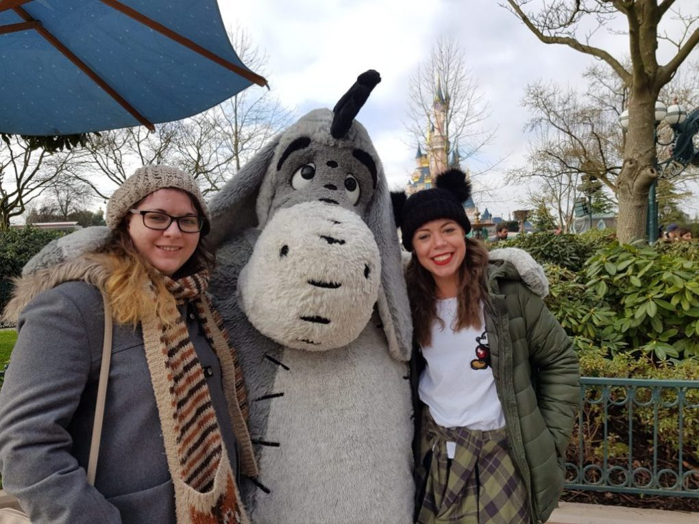 two young girls standing with arms round Eeyore character meet